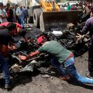 Civilians help a municipality bulldozer cleans up while citizens inspect the scene after a car bomb explosion at a crowded outdoor market in the Iraqi capital's eastern district of Sadr City, Iraq, Wednesday, May 11, 2016
