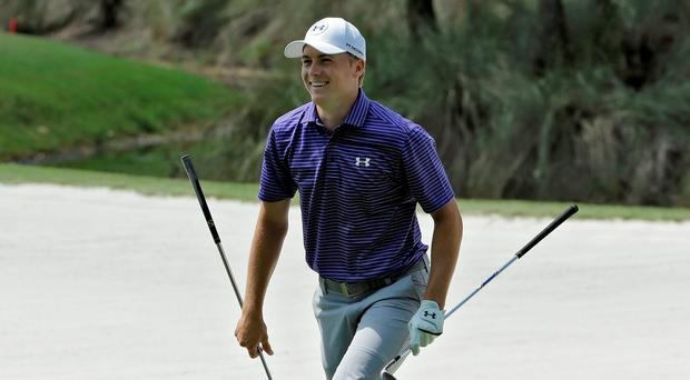 Jordan Spieth smiles after retrieving his sand wedge from a bunker on the 15th during a practice round for The Players Championship today at Sawgrass