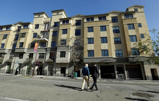 Berkeley Mayor Tom Bates, left, and Philip Grant, Irish Consul General of the Western United States, walk in front of the apartment block where the balcony tragedy occurred (AP Photo/Jeff Chiu)