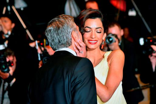 US actor George Clooney (L) kisses his wife, British-Lebanese lawyer Amal Clooney as they leave on May 12, 2016 the Festival Palace after the screening of the film