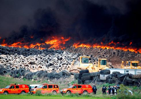Emergency workers stand next to a fire at a tire dump near a residential development in Sesena, south of Madrid, Spain, May 13, 2016