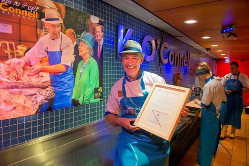 Fishmonger Pat O'Connell in the English Market on the anniversary of the Queen's visit to Cork with the iconic photograph of him sharing a joke with the monarch in the background. Photo: Michael Mac Sweeney/Provision