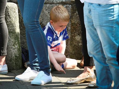 A young boy in Blessington colours playing in the shade of a guard of honour. Photo: Garry O'Neill