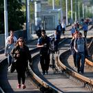 LONG ROAD AHEAD: Commuters walk the Luas line to Dublin city centre amid strike action. Photo: Laura Hutton/Collins Photo Agency