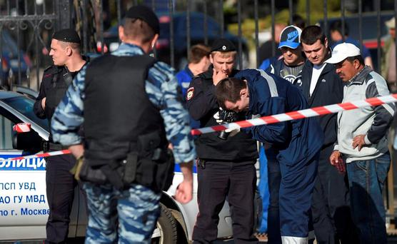 Police investigators work on the site of a brawl at the Khovanskoye cemetery in in Moscow, Russia. (AP Photo)