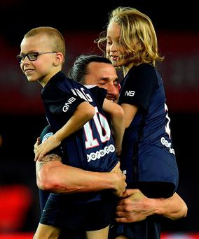 Paris Saint-Germain's Swedish forward Zlatan Ibrahimovic (C) holds his children at the end of the French L1 football match between Paris Saint-Germain and Nantes at the Parc des Princes stadium in Paris on May 14, 2016. AFP PHOTO / FRANCK FIFEFRANCK FIFE/AFP/Getty Images