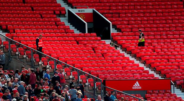 A sniffer dog patrols the stands after fans were evacuated from the ground prior to the Barclays Premier League match between Manchester United and AFC Bournemouth at Old Trafford (Photo by Alex Morton/Getty Images)