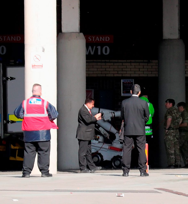 A robot rolls off the back of a bomb disposal truck under the grandstand of the stadium in Manchester. Photo: Getty