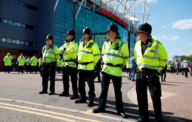 Police outside the stadium after the match was abandoned. Photo: Reuters
