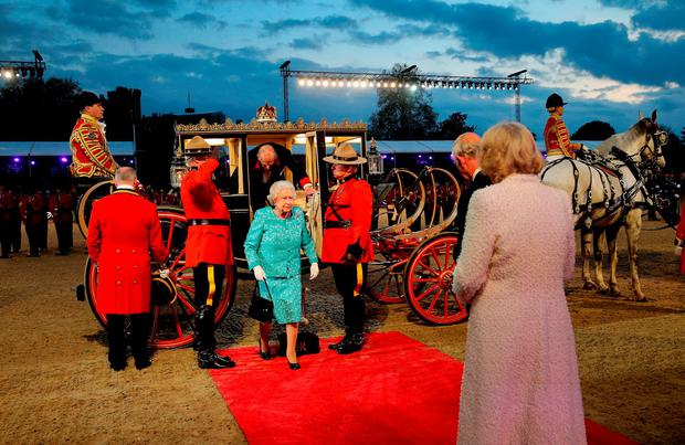 Queen Elizabeth II is greeted by the Prince of Wales and the Duchess of Cornwall as she arrives for the televised celebration of her 90th birthday in the grounds of Windsor Castle