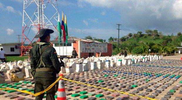 A Colombian national policeman stands guard in front of packages of cocaine, which were confiscated in Turbo province near the border with Panama, May 15, 2016
