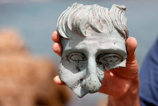 Part of a statue which was recovered from a merchant ship dated 1600 years old in the ancient harbor in the Caesarea National Park. Reuters/ Baz Ratner