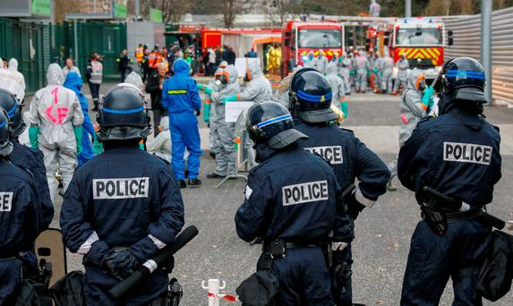 French police and firemen wearing chemical protective suits take part in a mock chemical attack exercise at the Geoffroy Guichard stadium in Saint-Etienne, France, in preparation of security measures for the UEFA 2016 European Championship. REUTERS/Robert Pratta/File Photo