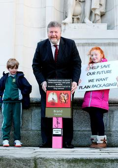 Dr James Reilly with Cathal Gray (7) and Aoife Gray (9) following the passing of the Plain Packaging Bill. Photo: Maxwells