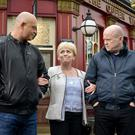 Grant & Phil take Peggy's arms and walk her home across the Square. Grant Mitchell (ROSS KEMP), Peggy Mitchell (BARBARA WINDSOR), Phil Mitchell (STEVE MCFADDEN) - (C) BBC - Photographer: Kieron McCarron
