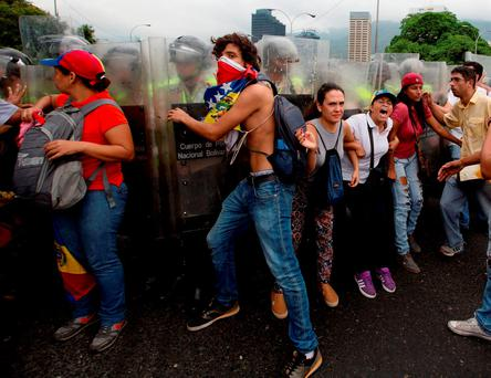 Anti-government demonstrators push against Bolivarian National Police blocking them from reaching the National Electoral Council (CNE) in Caracas, Venezuela