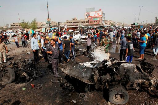Iraqi security forces and people gather at the site of a car bomb attack in Baghdad's mainly Shi'ite district of Sadr City, Iraq, May 17, 2016