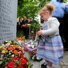 Haley O'Brien (4) who's great uncle John O'Brien was killed in the Dublin-Monaghan bombings, lays a wreath in Talbot Street Dublin, during a ceremony to mark the 42nd anniversary of the bombings. Photo: Niall Carson/PA Wire