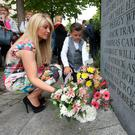 Wendy Doherty and her son Tyler (10), from Lucan, place flowers in memory of their mother and grandmother Colette Doherty and her unborn child at the 42nd anniversary of the Dublin and Monaghan bombings. Photo: Damien Eagers