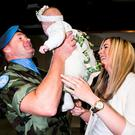 Pte Thomas Grant meets his 10-week-old daughter Sophia Grace for the first time with his partner Sinead Brennan in Dublin Airport after the 51th Infantry Group returned after spending 6 Months on a UNIFIL Tour in the Lebanon. Pic Kyran O'Brien
