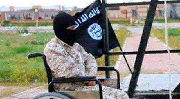 A man in a wheelchair sits beside one of Isil's victims. who is not shown in this photo