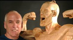 James O'Neal stands alongside his wood carving of Irish MMA star Conor McGregor
