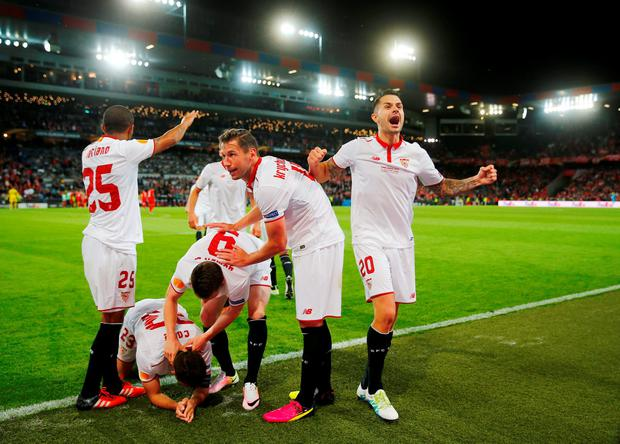 Coke celebrates with team mates after scoring the third goal for Sevilla