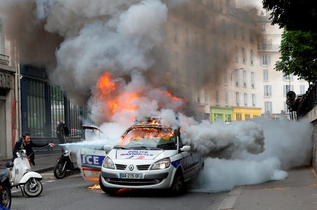 A man tries to pull off fire on a burning police car during clashes while police forces gather to denounce the almost daily violent clashes at protests against a labor reform, Wednesday, May 18, 2016 in Paris. Several hundred counter-demonstrators came by, chanting slogans like Everybody hates the police! and pushing up against the officers until eventually the police deployed pepper spray. (AP Photo/Francois Mori)