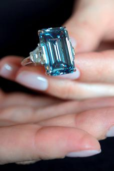 Christie's employee holds the Oppenheimer Blue diamond of 14.62 carats, which is estimated to be sold between 39 to 46 million US dollars, during a preview at the auction house Christie's, in Geneva, Switzerland. The auction will take place on Wednesday May 18, 2016 in Geneva. (Martial Trezzini/Keystone via AP,file)