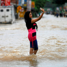 A woman takes a selfie while standing on a flooded road in Biyagama, Sri Lanka Photo: Dinuka Liyanawatte/Reuters