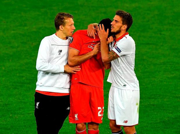 Liverpool's Emre Can is consoled by Daniel Carrico of Sevilla and teammate Lucas Leiva after last night's Europa League final. Photo: Dennis Grombkowski/Getty Images