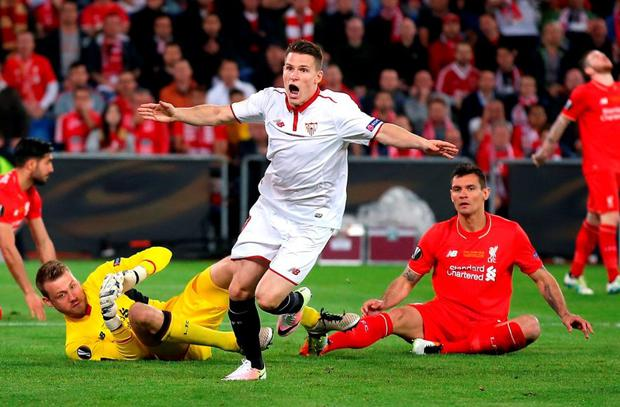 Liverpool duo Simon Mignolet and Dejan Lovren show their disappointment as Kevin Gameiro celebrates the opening goal in Sevilla's 3-1 win. Photo: Lars Baron/Getty Images