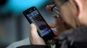 An investor checks stock information on a mobile phone at a brokerage house in Shanghai. Photo: Reuters