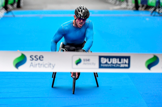 Patrick Monahan of Naas crosses the finish line to win the Wheelchair race at the SSE Airtricity Dublin Marathon 2014 Picture credit: Ramsey Cardy / SPORTSFILE