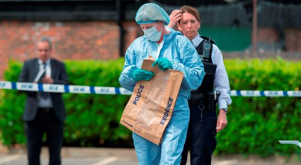 A forensic officer holding an evidence bag, at the scene. Photo: Stefan Rousseau/PA Wire