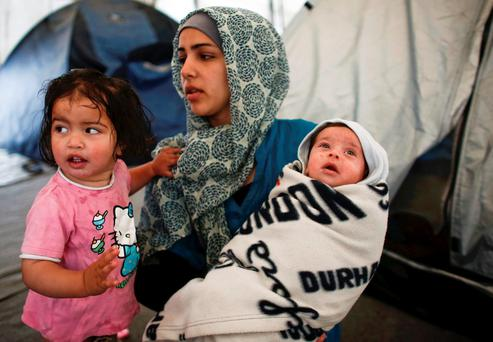 A Syrian refugee woman holds her 40-days old son as a girl stands with them at a makeshift camp for refugees and migrants at the Greek-Macedonian border near the village of Idomeni, Greece. Photo: Reuters