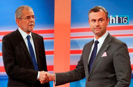 Presidential candidates Norbert Hofer of the Freedom Party (FPOe) and Alexander Van der Bellen (L) who is supported by the Greens party, shake hands before a TV debate. REUTERS/Heinz-Peter Bader