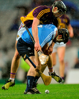 Dublin's David O'Callaghan finds himself carrying Eoin Conroy of Wexford on his back as both battle for a loose ball during Saturday's Leinster SHC quarter-final at Croke Park. Photo: Sportsfile