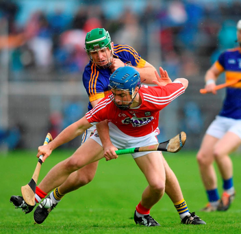 Cork's Conor O'Sullivan has little room to move as he is tackled by Noel McGrath of Tipperary. Photo: Sportsfile