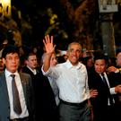 Barack Obama waves as he leaves after having a dinner with Anthony Bourdain at a restaurant in Hanoi. Photo: Reuters