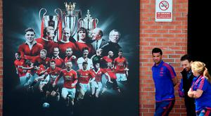 Club staff walk past a mural depicting present and past players and former managers outside Old Trafford yesterday. GETTY