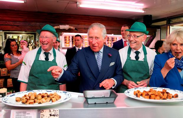 Britain's Prince of Wales and the Duchess of Cornwall sample award-winning sausages made by brothers Diarmuid (left) and Ernan McGettigan at McGettigan's butcher's shop in Donegal Town. Photo: Brian Lawless/PA Wire