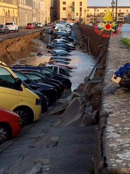 In this photograph provided by the Italian Firefighters Vigili del Fuoco, cars are engulfed by a chasm which opened along the Arno river near the Ponte Vecchio Old Bridge, seen in the background right, in Florence, Italy. (Vigili del Fuoco via AP)