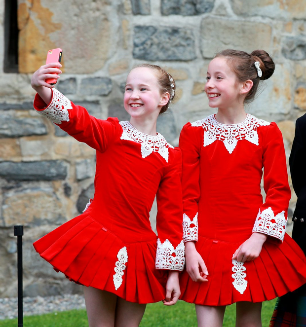 Dancers Ellie Ni Choilin (9) and Ailbhe Ni Loughley (11) take a picture of themselves before the visit by Prince Charles and Duchess Camilla to Donegal Castle. Photo: Frank McGrath