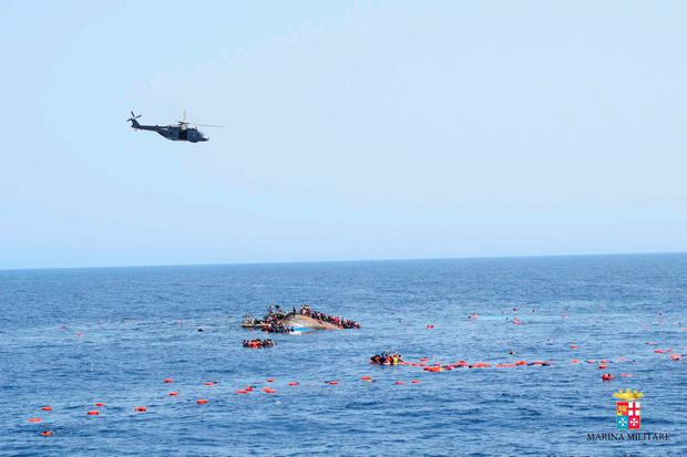 Migrants from a capsized boat are rescued during a rescue operation by Italian navy ships