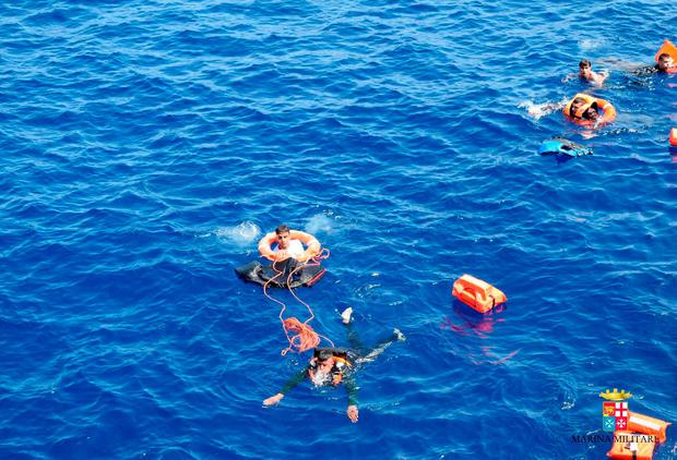 People swim after jumping out of a overturning boat off the Libyan coast, Wednesday, May 25, 2016. (Marina Militare via AP Photo)