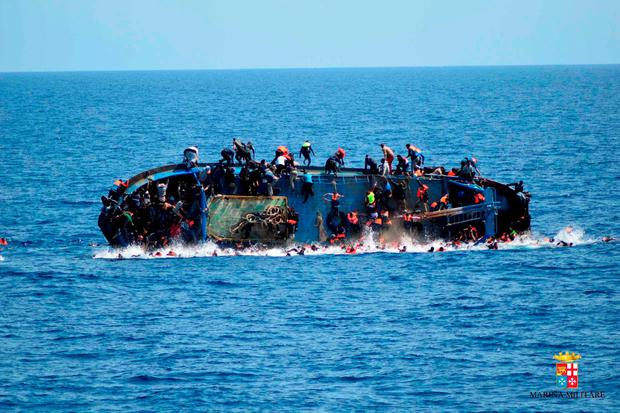 People jump out of a boat right before it overturns off the Libyan coast, Wednesday, May 25, 2016. (Marina Militare via AP Photo)