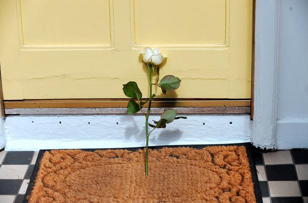 A rose is left at the deceased's door Picture: Caroline Quinn