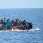 Migrants are thrown into the sea on a capsizing boat off the coast of Libya. Photo: Reuters