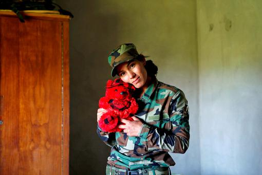 Yazidi female fighter Asema Dahir (21) poses with a teddy bear at a site near the frontline of the fight against Islil militants in Nawaran near Mosul, Iraq. Photo: Ahmed Jadallah/Reuters